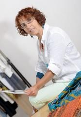 dressmaker look at a digital tablet in his workshop