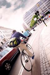 Fototapete - Man on bike in city traffic