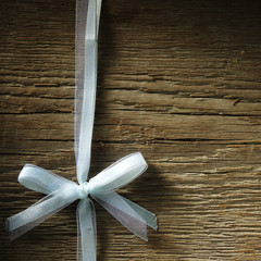 Decorative white ribbon and bow over wooden background