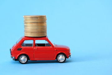 Coins on red miniature car