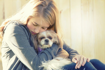 A sad or depressed teenage girl hugging a small dog