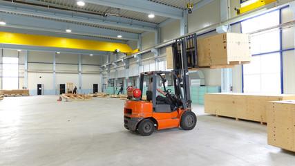 Gabelstapler hebt Holzkiste mit Waren in Industriehalle