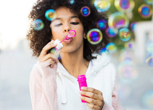 Afro woman blowing soap bubbles
