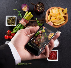 Hand taking photo of prepared food with smartphone