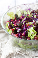 mixed salad on glass bowl with red beans, seeds, purple cabbage