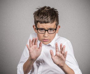 Headshot scared boy with glasses isolated on grey background