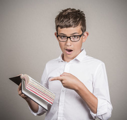 young man pointing at book page, shocked face expression