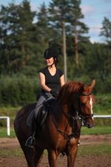 Portrait of brunette woman riding brown horse