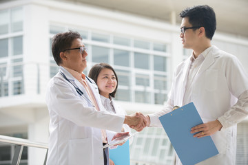 Asian medical team of doctors shaking hands inside hospital buil