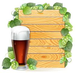 Hops branch and beer glass on a wooden background