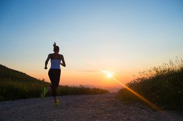 Fototapeta woman running on a mountain road at summer sunset obraz