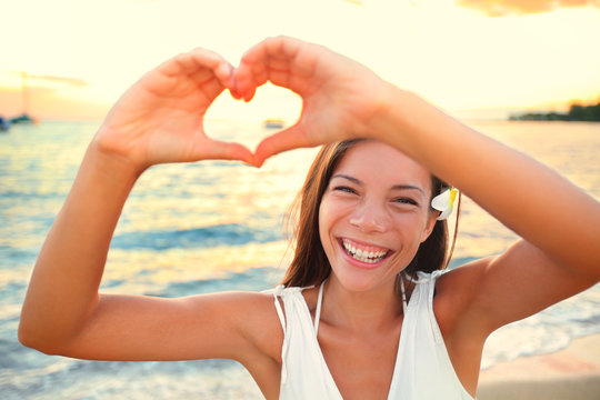 Love vacation - woman showing heart on beach