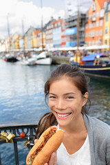 Woman eating traditional danish fast food hot dog
