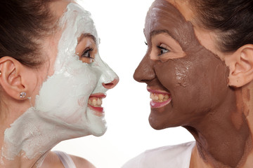 two silly young women with masks watch each other