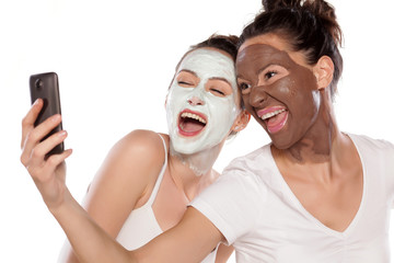 Two young women with masks making selfie