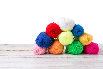 Colorful yarns on white wooden surface isolated