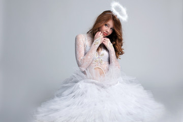 Image of pretty red-haired girl dressed as angel