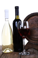 Wine in goblet and in bottles and wooden barrel