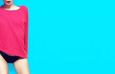 Portrait sexy fashion model pink sweater on blue background