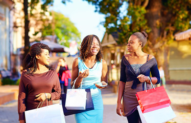 happy african girls walking the street with shopping bags