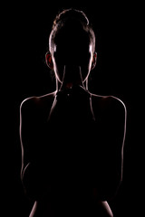 portrait of woman toushing lips with the hands in shadow
