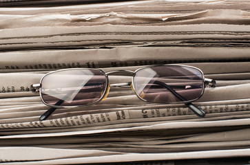newspaper with glasses closeup