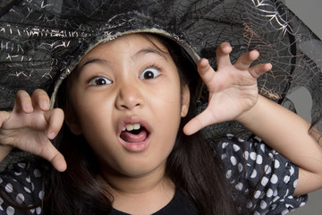 Portrait of little Asian girl in black hat and black clothing