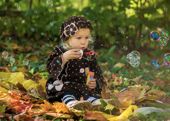 The little girl in park starts up soap bubbles