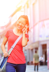 young asian woman on the phone walking at shopping street