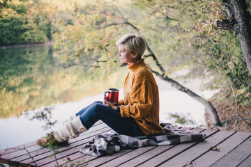 Poster Ontspanning Blond with blue eyes sitting near lake with cup of hot tea