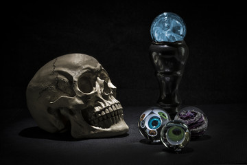 Skull and magic crystal balls with spooky eyes looking