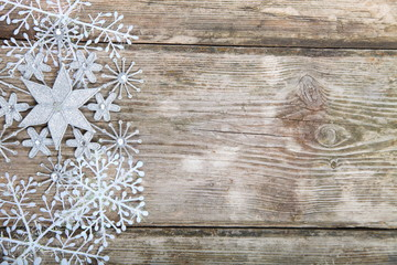 Snowflakes border on grunge wooden background.