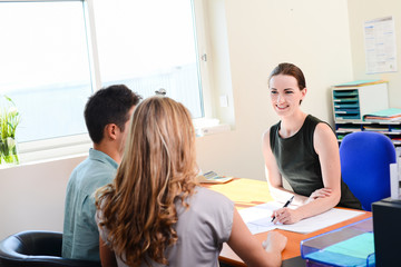 beautiful young business woman transaction with young couple