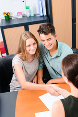 cheerful young couple with business woman handshaking