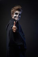 Teen with makeup skull showing thumbs up