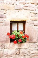 ventana con visillos y flores en pared de piedra.