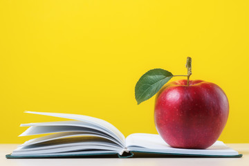 Red apple with green leaf on open notebook