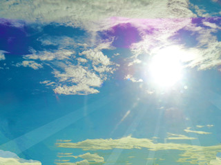 Sun rays on blue sky with clouds background