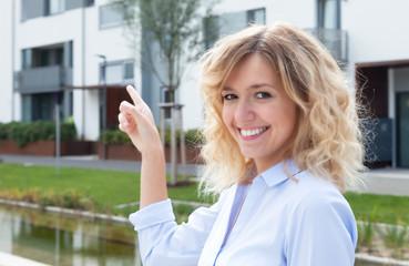 Frau mit blonden Locken zeigt ihre Traumwohnung