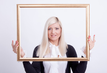 Portrait of a young blond woman holding a frame