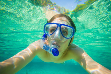 Portrait of man snorkeling in crystal clear laguna water on trop