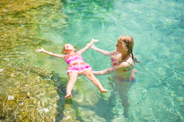 Young mother learn adorable daughter to relax in crystal clear l