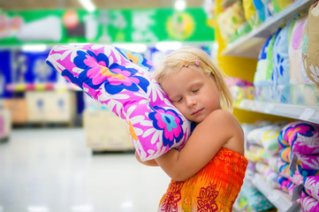 Adorable girl play with pillow, imitating sleep in department se