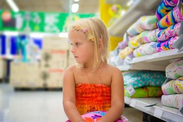 Adorable girl sit on floor near pillow shelves in department sec