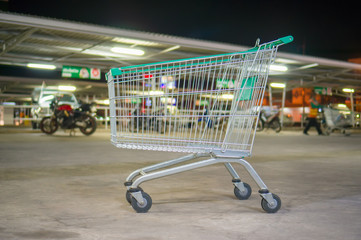 Empty shopping cart with green handle on parking near supermarke