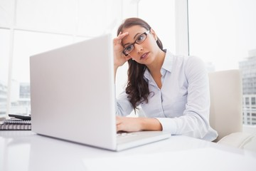 Focused businesswoman using laptop at desk