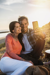 Romantic couple sitting on the beach at sunset and taking a self