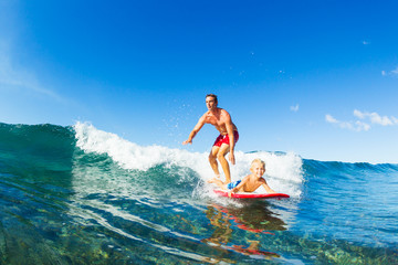 Fototapete - Father and Son Surfing, Riding Wave Together
