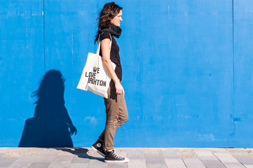Young girl dressed in brown chinos, sneakers on blue background