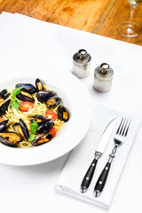 White plate of italian pasta with mussels, cherry tomato  and he